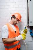 Hezký elektrikář v rukavicích oprava kabeláže v blízkosti rozvaděče
