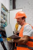 Boční pohled na elektrikáře, jak si sundává rukavici a drží notebook v blízkosti rozvaděče