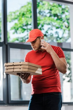 Delivery man in cap talking on smartphone and holding pizza boxes stock vector