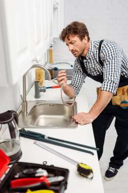 Selective focus of plumber in overalls holding metal pipe near sink in kitchen stock vector