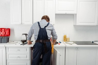 Back view of plumber in overalls working in kitchen stock vector
