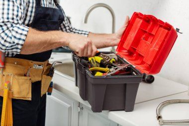 Cropped view of workman in overalls opening toolbox on kitchen worktop stock vector