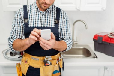 Cropped view of workman in tool belt using smartphone while working in kitchen stock vector