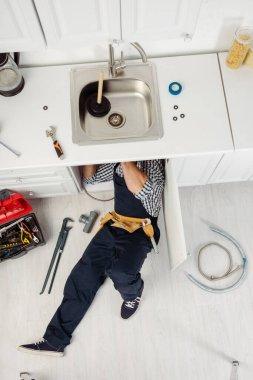 Top view of plumber in workwear fixing kitchen sink near tools on floor stock vector