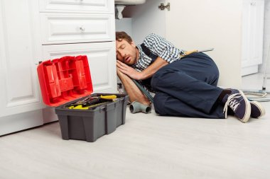 Plumber sleeping on floor near toolbox and sink in kitchen stock vector
