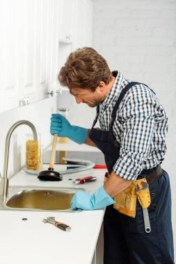 Side view of plumber in rubber gloves holding plunger while fixing kitchen sink stock vector