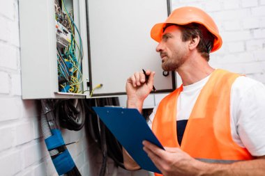 Selective focus of handsome electrician in safety vest and hardhat holding pen and clipboard while looking at electric panel