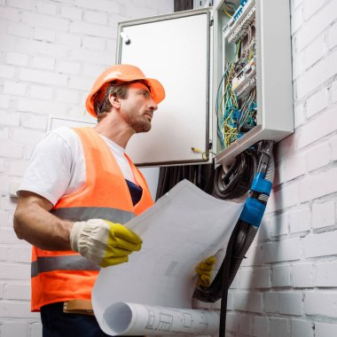 Handsome electrician holding blueprint and looking at electrical distribution box