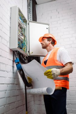 Electrician in hardhat and safety vest holding blueprint and looking at electric panel
