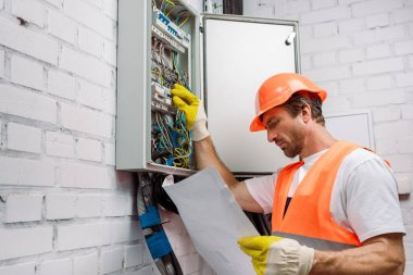 Handsome electrician in gloves looking at blueprint and fixing electrical distribution box