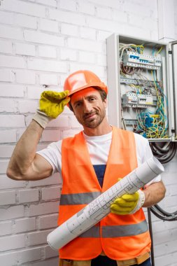 Handsome repairman in hardhat looking at camera while holding blueprint near electrical distribution box stock vector