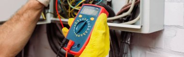 Panoramic crop of electrician using multimeter near electrical distribution box