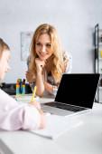 Selektiver Fokus einer lächelnden Frau, die ein Kind beim Schreiben auf einem Copybook in der Nähe eines Laptops mit leerem Bildschirm beobachtet