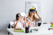 Fotografie Selective focus of smiling mother and kid using vr headsets during online education at home