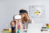 Selektiver Fokus einer lächelnden Frau, die ihre Tochter umarmt, während sie Virtual-Reality-Headsets in der Nähe von Laptop und Büchern verwendet