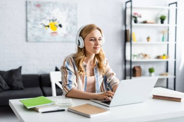 Selective focus of pretty woman working with laptop and headphones