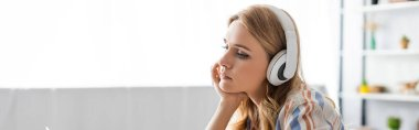Panoramic shot of pensive woman using headphones