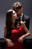 Fotografie Schöner Mann im Anzug umarmt sinnliche Frau in rotem Kleid auf grau