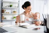 szelektív fókusz boldog nő holding cup közel aranyos csecsemő fia és szerkentyűk