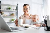 szelektív fókusz boldog anya holding cup közel aranyos csecsemő fia és szerkentyűk