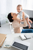 selektivní zaměření šťastný matka držení v náručí roztomilý kojenec syn v blízkosti notebooku