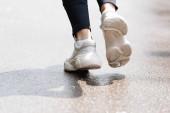 Ausgeschnittene Ansicht einer Sportlerin in weißen Turnschuhen, die nach draußen läuft