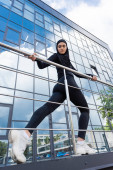 low angle view of arabian woman in hijab holding handrail while working out near modern building