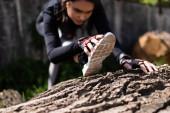 selektivní zaměření mladé sportovkyně cvičení na kmen stromu