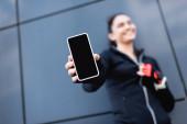 szelektív fókusz fiatal sportoló gazdaság smartphone üres képernyőn