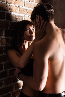 Sensual woman in lingerie touching shirtless boyfriend near brick wall stock vector