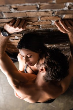 Overhead view of shirtless man kissing sexy girlfriend near brick wall at home
