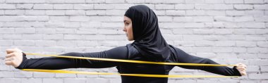 horizontal image of arabian sportswoman in hijab exercising with resistance band