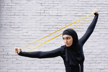 arabian sportswoman in hijab exercising with resistance band near brick wall