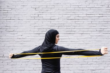 arabian woman in hijab exercising with resistance band near brick wall