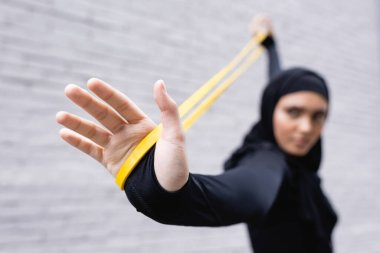 selective focus of arabian sportswoman in hijab exercising with resistance band near brick wall