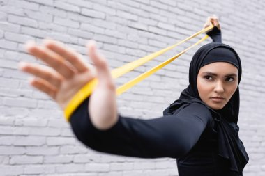 selective focus of arabian woman in hijab exercising with resistance band near brick wall
