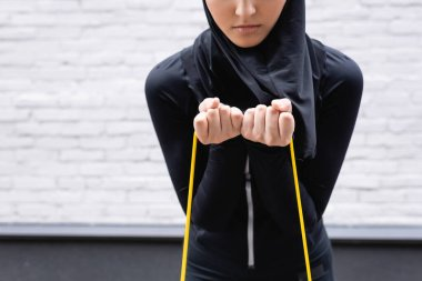 cropped view of arabian sportswoman in hijab exercising with resistance band near brick wall