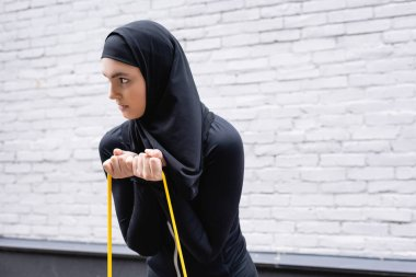 arabian girl in hijab exercising with resistance band near brick wall