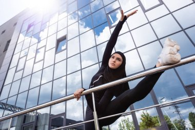 Low angle view of muslim woman in hijab holding handrail while exercising near modern building stock vector