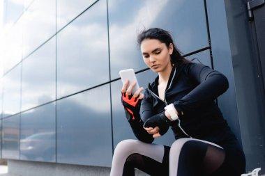 Genç sporcu kadın akıllı telefon tutuyor ve fitness izleyicisine bakıyor.