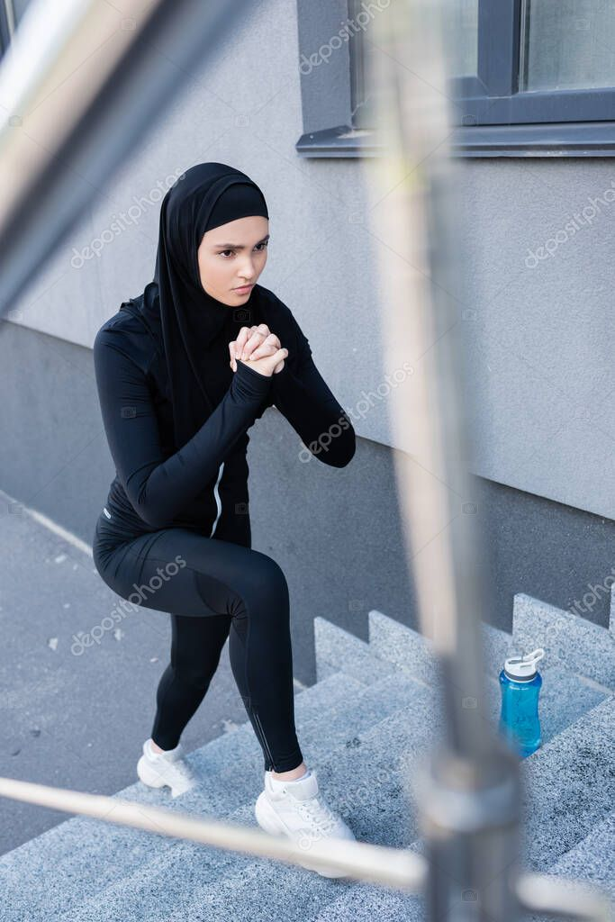 Selective focus of muslim woman in hijab exercising on stairs near sports bottle stock vector