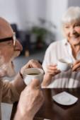 Szelektív fókusz a pozitív idős pár kávézás a konyhában