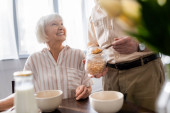 Selective focus of senior woman smiling at husband pouring cereals from jar during breakfast