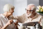 Válogatott fókusz a vezető férfi kezében újság és átölelő mosolygós feleség egy csésze kávét