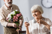 Selective focus of smiling woman holding cup of coffee and using smartphone near husband with bouquet