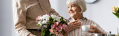 Panoramic shot of senior man giving bouquet to smiling wife with cup of coffee