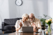 Selective focus of smiling senior couple waving hands during video call on laptop at home