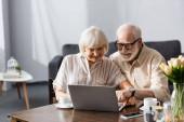 Szelektív fókusz mosolygó idős pár laptoppal közel kávécsésze az asztalon