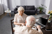 Selective focus of senior woman smiling at husband using laptop near coffee and smartphone on table