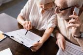 Vysoký úhel pohledu seniora muž mluví na smartphone poblíž manželky ukazuje na dokument s nápisem vymáhání dluhů